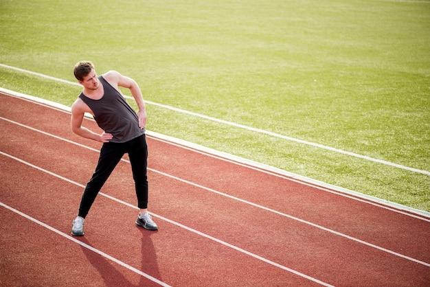Portret robi ćwiczyć na biegowym śladzie sportowiec
