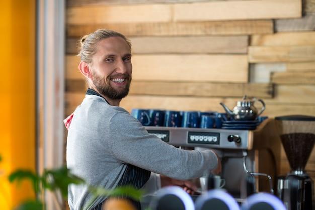 Portret robi filiżance kawy uśmiechnięty kelner