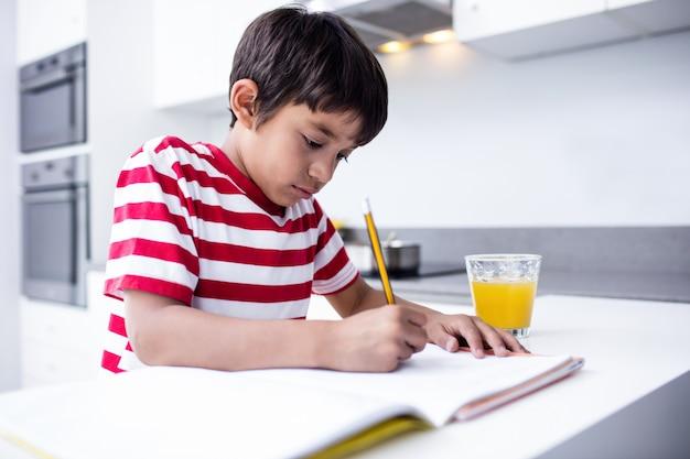 Portret robi pracie domowej w kuchni chłopiec
