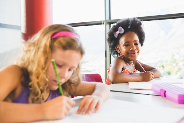 Portret robi pracie domowej w sala lekcyjnej dziewczyna