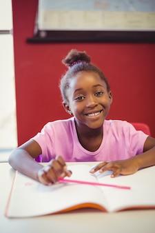 Portret robi pracie domowej w sala lekcyjnej uczennica