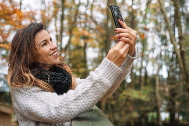 Portret robi selfie w jesień parku pełnym żółci liście szczęśliwa kobieta.