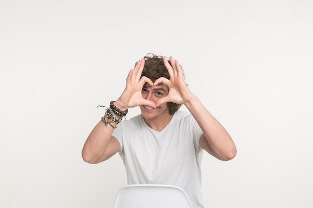 Portret robi sercu z palcami na białym tle szczęśliwy przystojny młody człowiek