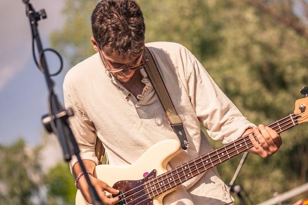 Portret rockmana grającego na akustycznym basie i śpiewającego