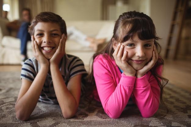 Portret rodzeństwa kłama na dywaniku w żywym pokoju