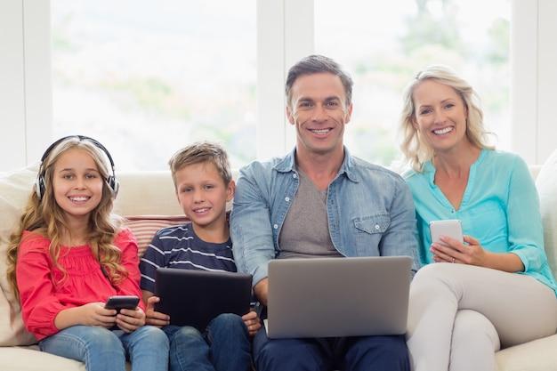Portret rodzice i dzieciaki siedzi na kanapie z laptopem, telefonem komórkowym i cyfrową pastylką