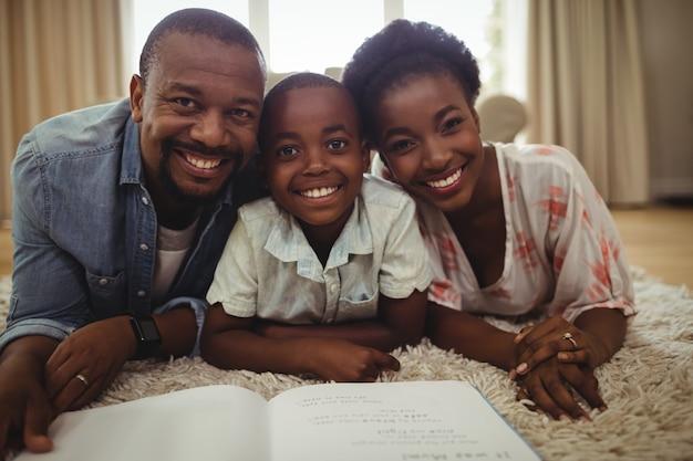Portret rodzice i syn czyta książkę podczas gdy kłamający na dywaniku