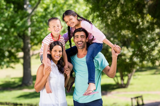 Portret rodzice niesie ich dzieci na ramieniu w parku
