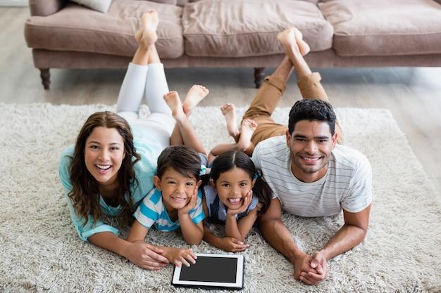 Portret rodziców i dzieci leżąc na dywanie i za pomocą cyfrowego tabletu