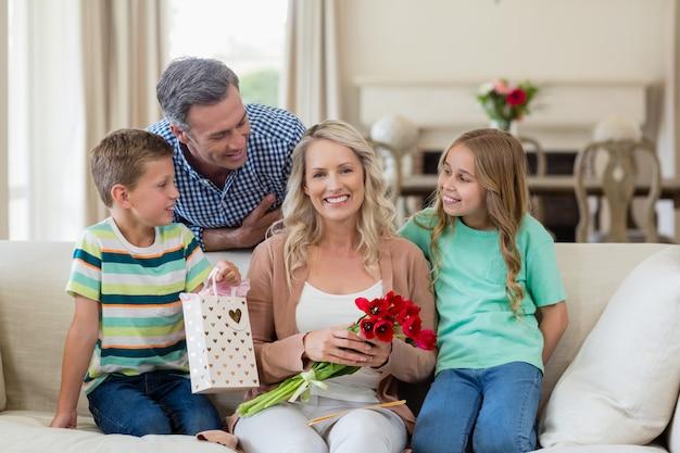 Portret rodziców i dzieci siedząc na kanapie z teraźniejszością w salonie
