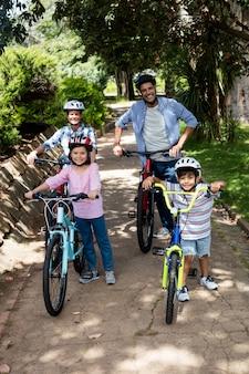 Portret rodziców i dzieci stojących z rowerem w parku