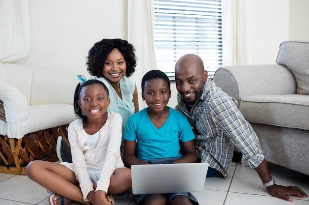 Portret rodziców i ich dzieci za pomocą laptopa w salonie