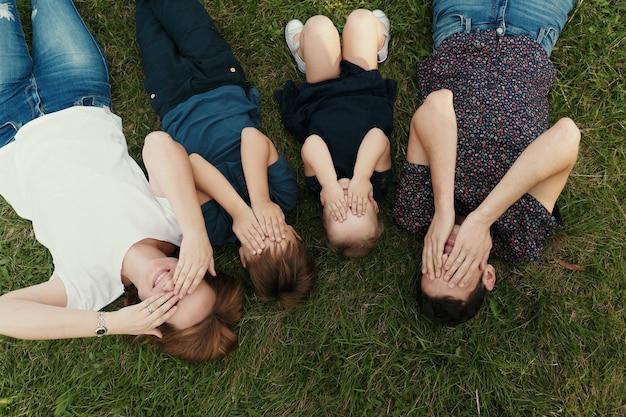 Portret rodzina z dzieciakami kłama na trawie