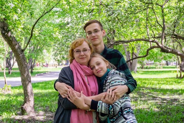 Portret rodzinny - matka z dwójką nastoletnich dzieci w parku na świeżym powietrzu