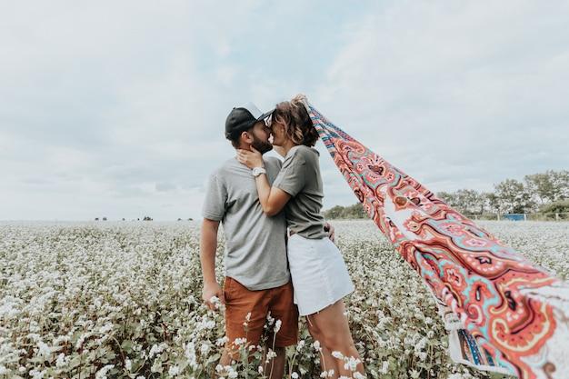 Portret rodzinny młodej pary piękny na białym polu z kwiatami. koncepcja chodzenia stylu życia. kreatywny portret rodziny na boisku