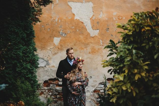 Portret rodzinny, para obrażająca. mężczyzna przytula delikatną kobietę w ciąży