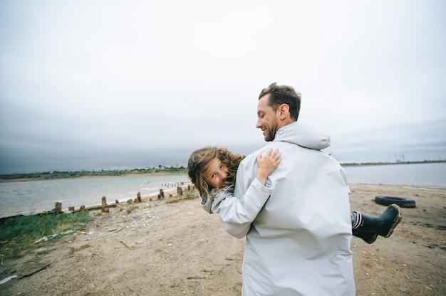 Portret rodzinny taty i dauthera w płaszczu w pobliżu morza