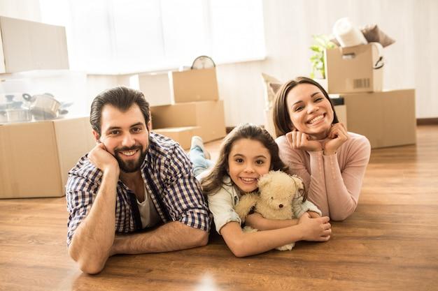 Portret rodzinny trzech osób leżących na podłodze. mężczyzna, kobieta i ich córka wyglądają na wesołych i szczęśliwych. za nimi jest wiele pudeł.