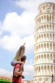 Portret rodzinny w tle wieża edukacyjna. piza - podróż do znanych miejsc w europie.