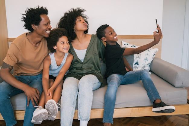 Portret rodziny afroamerykanów przy selfie wraz z telefonem komórkowym w domu