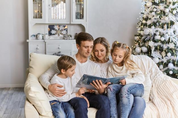 Portret rodziny czytanie książki na boże narodzenie wieczorem