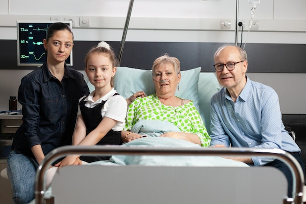 Portret rodziny odwiedzającej emerytowaną babcię, patrzącą w kamerę