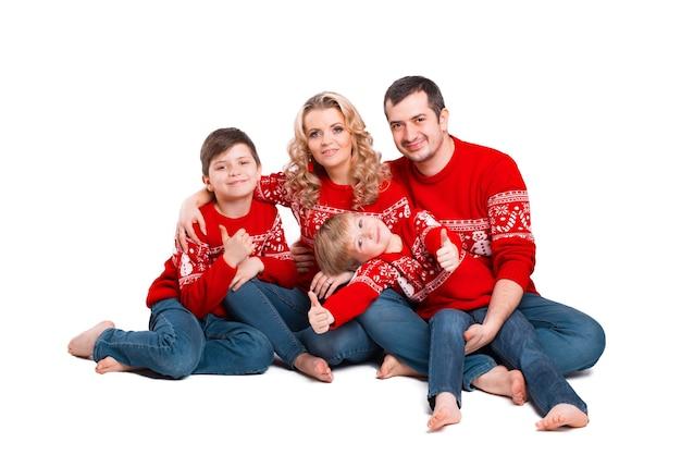 Portret rodziny siedzi razem w ubrania świąteczne, patrząc i uśmiechnięte