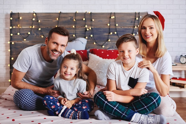 Portret rodziny spędzając boże narodzenie rano w łóżku
