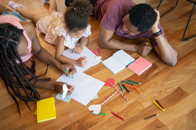 Portret rodziny spędzającej razem czas i rysując na podłodze podczas pobytu w domu