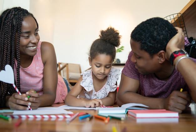 Portret rodziny spędzającej razem czas i rysując na podłodze podczas pobytu w domu.