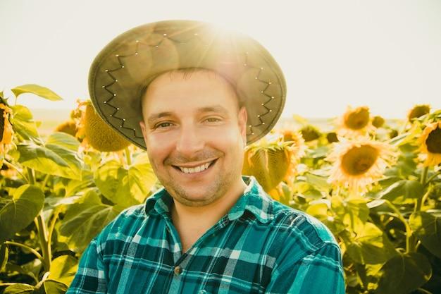 Portret rolnika na polu słoneczników i patrzący na kamerę młody rolnik stoi i uśmiecha się...