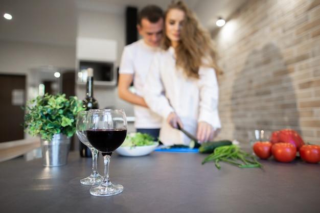Portret romantyczna para w kuchni w domu. blondynki kobieta z długie włosy plasterkami ogórkowymi. mężczyzna tulący kobietę z boku