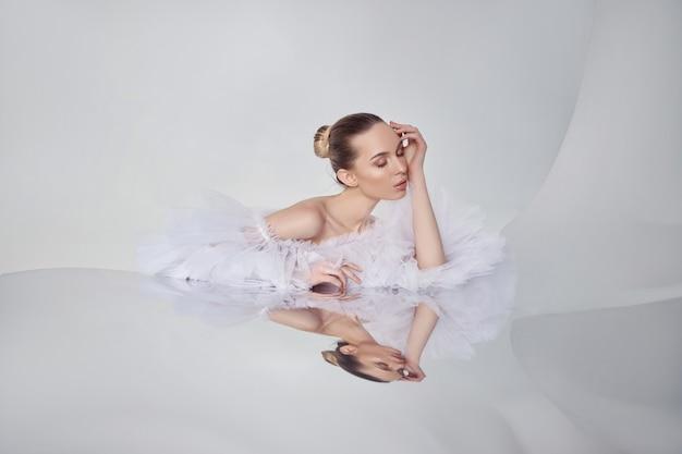 Portret romantycznej urody kobiety w lekkiej sukience odbija się w lustrze. kosmetyki naturalne, piękna gładka skóra twarzy, kok do włosów