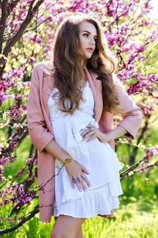 Portret romantycznej wrażliwej młodej kobiety z długimi włosami w różowym płaszczu