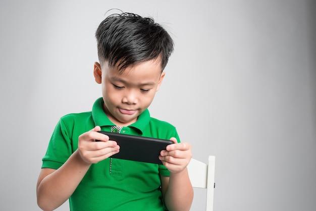Portret rozbawione słodkie małe dziecko grając w gry na smartfonie na białym tle