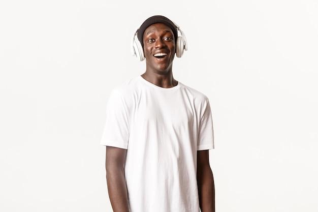 Portret rozbawiony i szczęśliwy afroamerykanin młody chłopak słucha podcastu lub muzyki w słuchawkach, uśmiechając się zadowolony