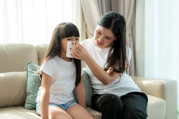 Portret rozciętej azjatyckiej dziewczyny dmuchającej smark w serwetkę z matką trzyma ją ostrożnie przy nosie.