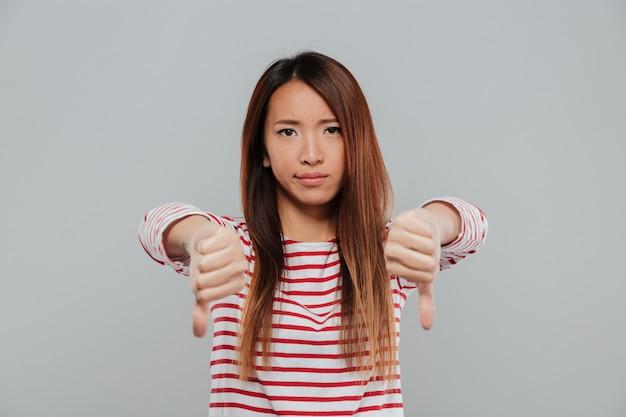 Portret rozczarowana azjatykcia kobieta pokazuje kciuki zestrzela