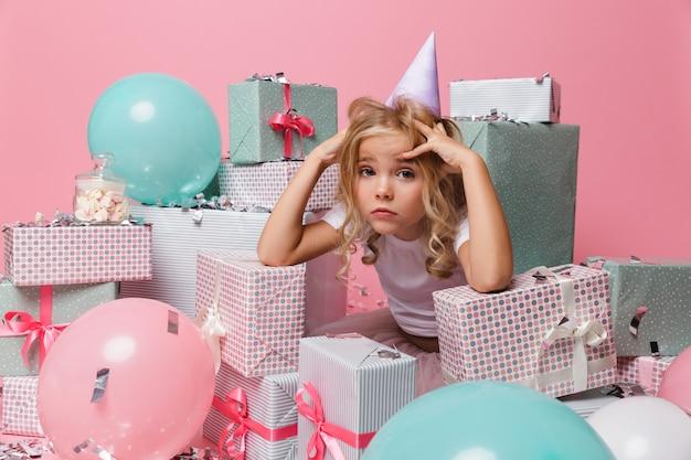 Portret rozczarowana mała dziewczynka w urodzinowym kapeluszu