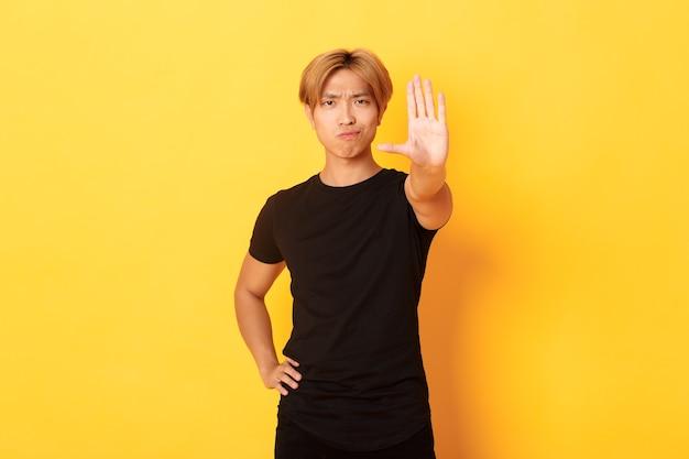 Portret rozczarowanego, poważnego azjaty, uśmiechającego się niezadowolonego i wyciągającego rękę, pokazującego gest stop, żółta ściana