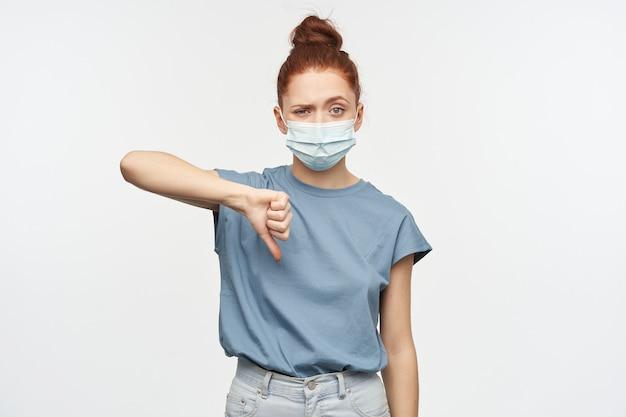 Portret rozczarowanej dziewczyny rude włosy zebrane w kok. ubrana w niebieską koszulkę i maskę ochronną. pokazywanie kciuka w dół w sprzeciwie. pojedynczo na białej ścianie