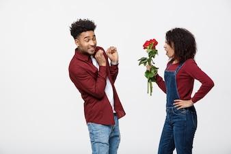 Portret rozczarowanej młodej kobiety mienia czerwieni róża podczas gdy gniewny na jej chłopaku.