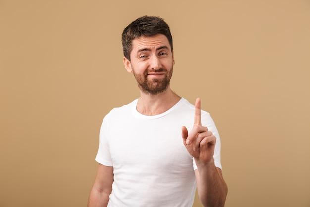 Portret rozczarowany młody człowiek ubrany niedbale pokazując gest stop na białym tle nad beżem
