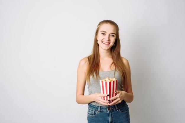Portret roześmiana dziewczyna trzyma popkornu pudełko i patrzeje kamerę na biel ścianie w przypadkowych ubraniach. piękna kobieta patrzeje ono uśmiecha się i kamerę. copyspace, szablon do bloga