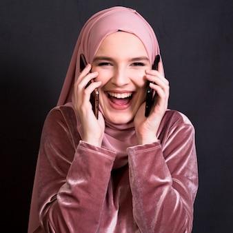 Portret roześmiana kobieta patrzeje kamerę podczas gdy opowiadający na telefonie komórkowym