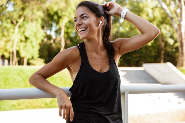 Portret roześmiana sprawności fizycznej kobieta opiera na poręczu