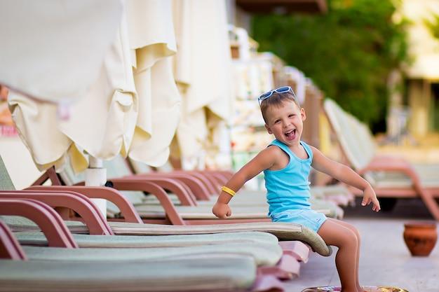 Portret roześmianego chłopca z kołem ratunkowym na tle basenu blisko hotelu w lecie na wakacje.