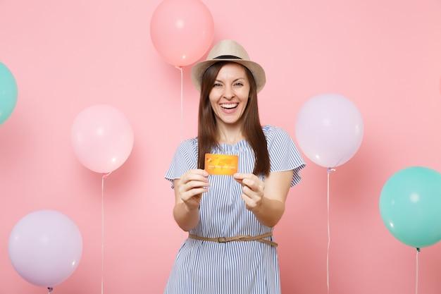 Portret roześmianej fascynującej młodej kobiety w słomkowym letnim kapeluszu i niebieskiej sukience, trzymając kartę kredytową na pastelowym różowym tle z kolorowymi balonami. urodziny wakacje ludzi szczerych emocji.