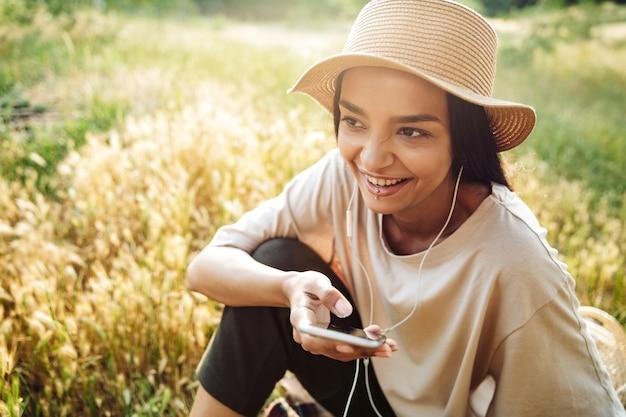 Portret roześmianej kobiety noszącej przekłuwanie warg za pomocą telefonu komórkowego i słuchawek, siedząc na trawie w zielonym parku