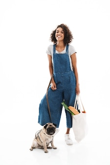 Portret roześmianej kobiety trzymającej torbę na zakupy z produktami spożywczymi i stojącej z jej mopsem odizolowanym nad białą ścianą